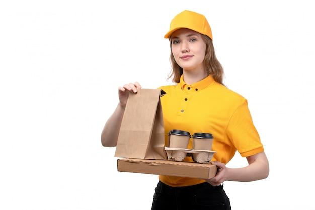 Widok z przodu młody żeński kurier żeński pracownik usług dostawy żywności trzymając filiżanki kawy uśmiecha się na białym tle