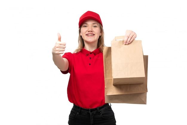 Widok z przodu młody żeński kurier żeński pracownik usług dostawy żywności uśmiecha się gospodarstwa dostawy pakietów na białym tle