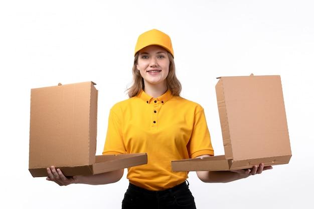 Widok z przodu młody żeński kurier żeński pracownik usług dostawy żywności uśmiecha się gospodarstwa pola żywności na białym tle