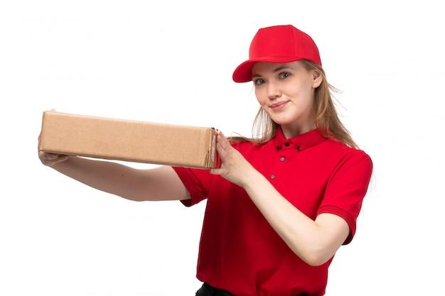 Widok z przodu młody żeński kurier żeński pracownik usług dostawy żywności uśmiecha się pole gospodarstwa z jedzeniem na białym tle