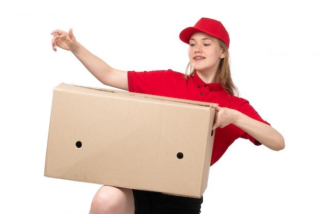 Widok z przodu młody żeński kurier żeński pracownik usług dostawy żywności uśmiecha się posiadający ogromne pole dostawy na białym tle