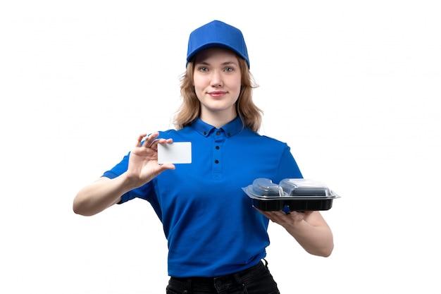 Widok z przodu młody żeński kurier żeński pracownik usług dostawy żywności uśmiecha się trzymając białą kartę i miskę z jedzeniem na białym tle