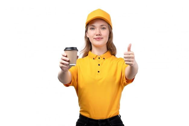 Widok z przodu młody żeński kurier żeński pracownik usług dostawy żywności uśmiecha się trzymając filiżankę kawy na białym tle