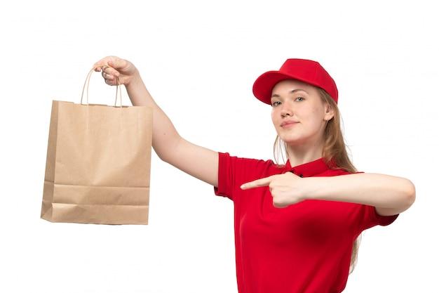 Widok z przodu młody żeński kurier żeński pracownik usług dostawy żywności uśmiecha się trzymając pakiet dostawy żywności na białym tle