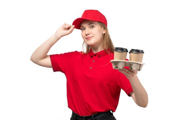 Widok z przodu młody żeński kurier żeński pracownik usług dostawy żywności uśmiechnięta gospodarstwa cupf kawy na białym tle