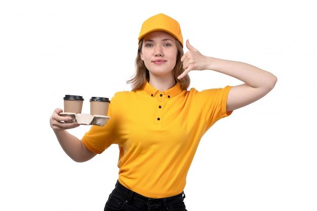 Widok z przodu młody żeński kurier żeński pracownik usług dostawy żywności uśmiechnięte gospodarstwa filiżanki kawy na białym tle