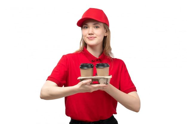 Widok z przodu młody żeński kurier żeński pracownik usług dostawy żywności uśmiechnięty gospodarstwa filiżanki dostawy kawy na białym tle