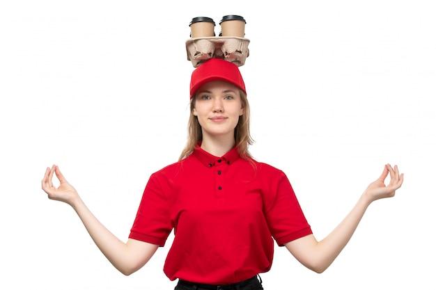 Widok z przodu młody żeński kurier żeński pracownik usług dostawy żywności uśmiechnięty w medytacji stanowią z filiżankami kawy na głowie na białym tle