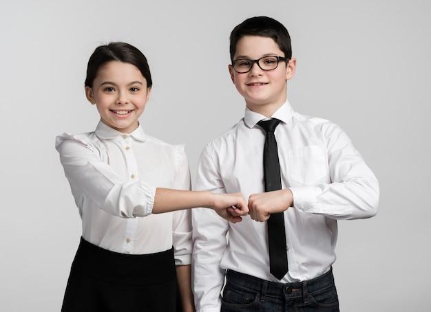 Widok z przodu młodych dzieci biznesowych stwarzających