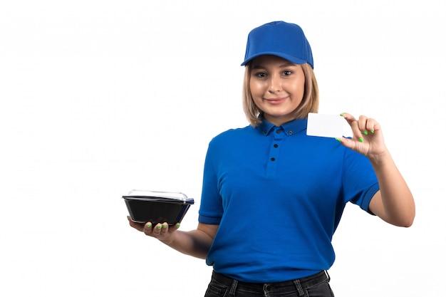 Widok z przodu młodych kobiet kurier w niebieskim mundurze, trzymając miskę z jedzeniem i białą kartę
