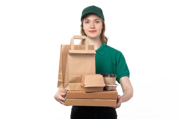 Widok z przodu młodych kobiet kurier w zielonym mundurze, trzymając opakowania kawy filiżanki żywności i uśmiechając się na białym tle
