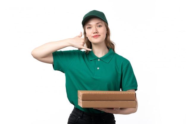 Widok z przodu młodych kobiet kurier w zielonym mundurze, trzymając pudełka po pizzy i uśmiechnięte