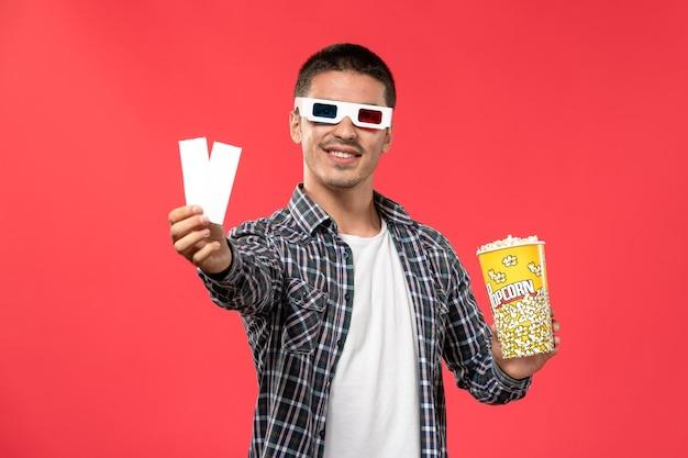 Widok z przodu młodych męskich okularów przeciwsłonecznych in -d posiadających pakiet popcornu i bilety na jasnoczerwoną ścianę kino kino film męski