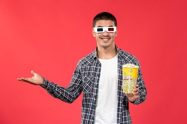 Widok z przodu młodych mężczyzn w okularach przeciwsłonecznych d, trzymając pakiet popcornu i uśmiechając się na jasnoczerwonej ścianie męskich filmów kinowych