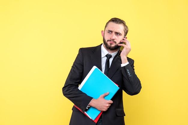 Widok z przodu młodzieńca w czarnym garniturze czeka na odebranie telefonu i trzymając foldery na żółto