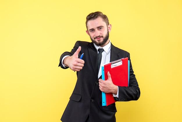 Widok z przodu młodzieńca w czarnym garniturze, patrząc zadowolony, trzymając czerwony schowek i niebieski folder, robiąc znak ok, stojąc na żółtym