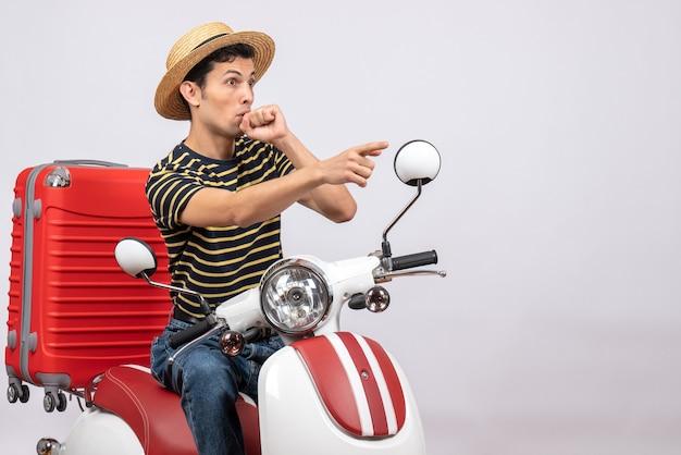 Widok z przodu młodzieńca w słomkowym kapeluszu na motorowerze, zastanawiając się