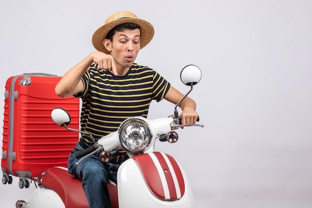Widok z przodu młodzieńca ze słomkowym kapeluszem na motorowerze, wskazując palcami poniżej