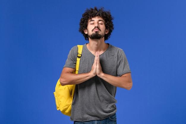 Widok z przodu modlącego się na niebieskiej ścianie młodego mężczyzny w szarej koszulce w żółtym plecaku