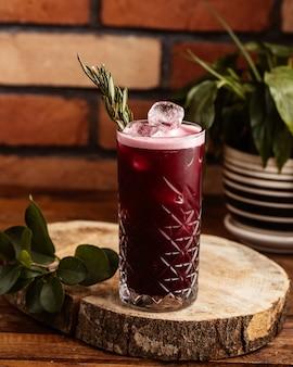 Widok z przodu mrożony koktajl wiśniowy z kostkami lodu na brązowym drewnianym biurku pić koktajl sokowy