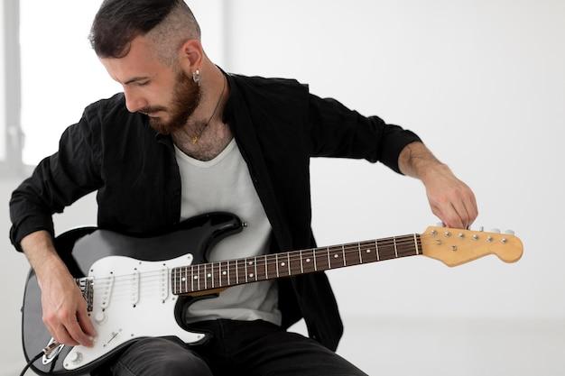 Widok z przodu muzyk grający na gitarze elektrycznej
