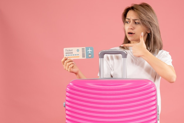 Widok z przodu mylić młoda kobieta, wskazując na bilet za różową walizką