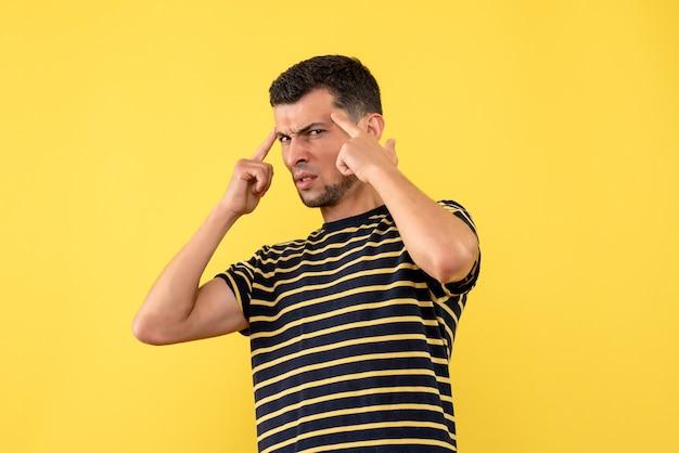 Widok z przodu mylić młody człowiek w czarno-białe paski t-shirt na białym tle żółty
