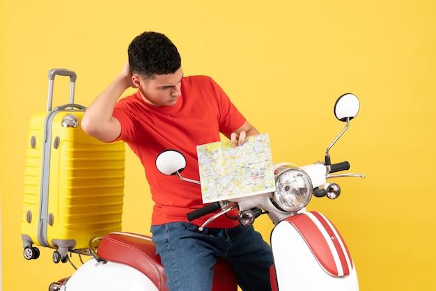 Widok z przodu mylić przystojny mężczyzna na motorowerze patrząc na mapę