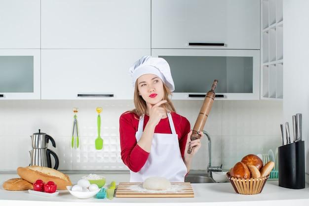 Widok z przodu myśląca kobieta szefa kuchni trzymająca wałek do ciasta w kuchni