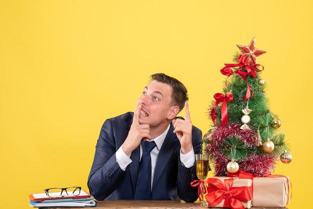 Widok z przodu myślącego człowieka siedzącego przy stole w pobliżu choinki i przedstawia na żółto