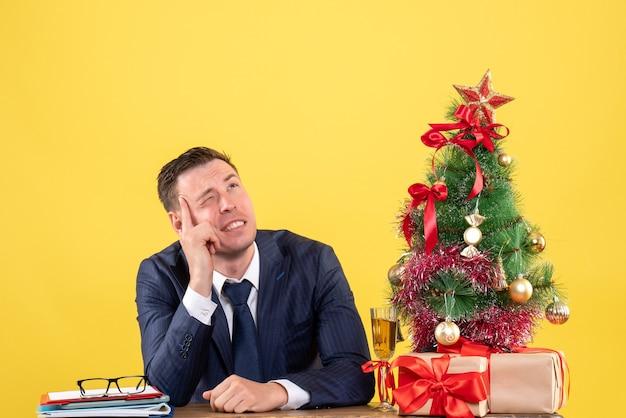 Widok z przodu myślącego człowieka z mrugniętymi oczami siedzącego przy stole w pobliżu choinki i prezentów na żółto