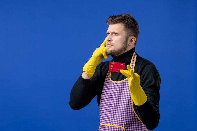 Widok z przodu myślącego młodego mężczyzny trzymającego kartę stojącą na niebieskiej ścianie
