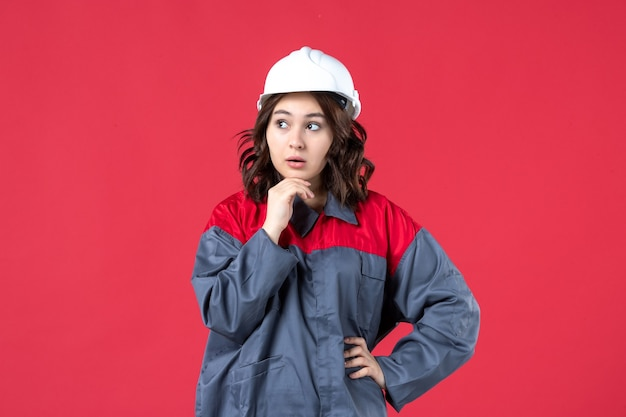 Widok z przodu myślącej kobiety budowniczej w mundurze z twardym kapeluszem na na białym tle czerwonym tle