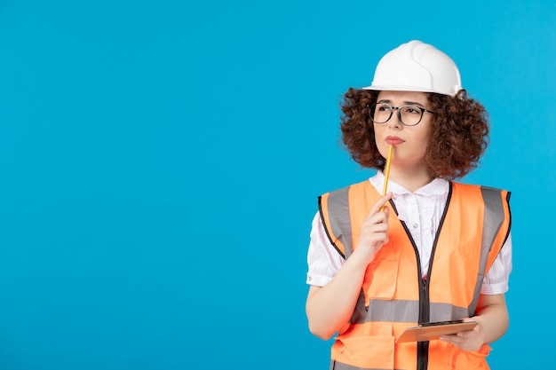 Widok z przodu myśli żeński konstruktor w mundurze i hełmie na niebieskiej ścianie