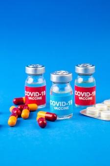 Widok z przodu na ampułki i kapsułki szczepionki przeciwko covid zapakowane w pigułki na tle niebieskiej fali