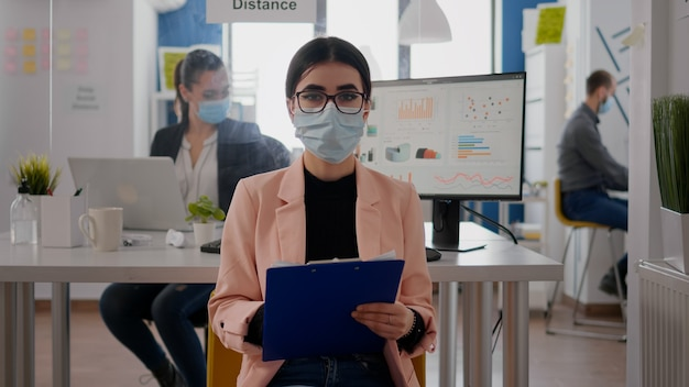 Widok z przodu na bizneswoman noszącą maskę na twarz podczas rozmowy na spotkaniu wideo online, zespół pracujący w tle, zachowujący dystans społeczny, aby uniknąć zakażenia covid19. herbata konferencyjna zoom
