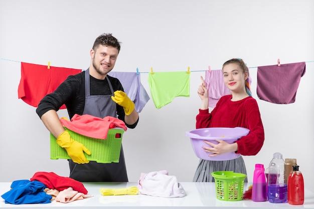 Widok z przodu na czas prania mężczyzny i jego żony trzymających środki do prania za obrusami na linie na białej ścianie