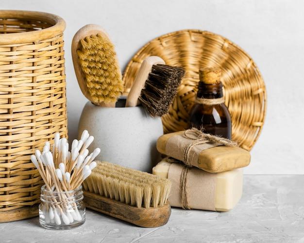 Widok z przodu na ekologiczne środki czystości w zestawie ze szczoteczkami i wacikami