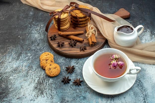 Widok z przodu na filiżankę czarnej herbaty i ułożone ciasteczka z cynamonowymi limonkami na lodowym tle
