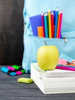 Widok z przodu na przybory szkolne z jabłkiem i kolorowymi ołówkami