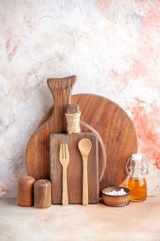 Widok z przodu na różne deski do krojenia drewniane łyżki mała butelka oleju na kolorowej powierzchni