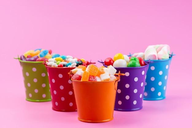 Widok z przodu na różne słodycze, takie jak konfitury, marmolady, cukierki wewnątrz koszy w różowym, cukrowo słodkim kolorze