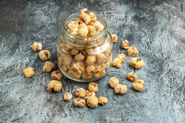 Widok z przodu na słodki popcorn w szklanej puszce na jasnym tle