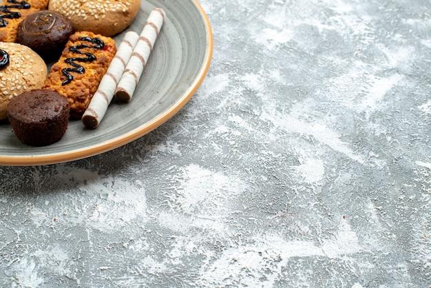 Widok z przodu na słodkie ciasteczka wewnątrz talerza na jasnej, białej przestrzeni