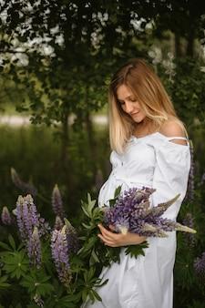 Widok z przodu na spokojną kobietę w ciąży ubraną w białą sukienkę z dzikim bukietem łubinu i patrzącą na brzuch