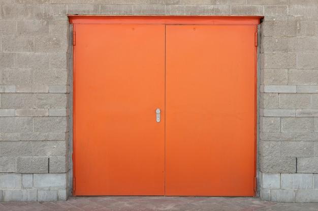Widok z przodu na szerokie pomarańczowe lub jaskrawoczerwone drzwi w szarym kamiennym murem z obrzeżami