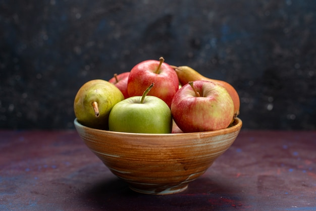 Widok z przodu na talerz z owocami, gruszkami i jabłkami na ciemnym biurku owoce dojrzałe, świeża, łagodna witamina