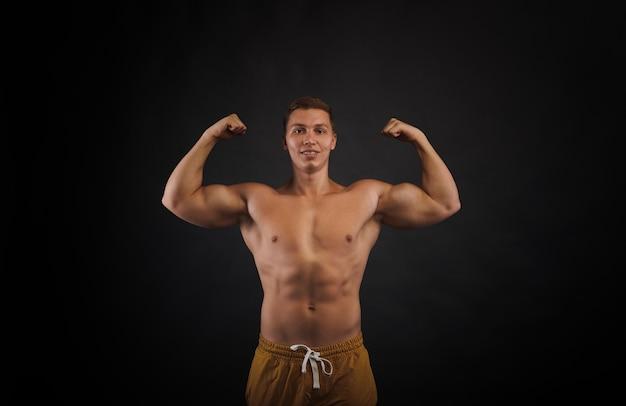 Widok z przodu na tułów wyszkolonego kulturysty. mężczyzna pokaż bicepsy. portret napompowany mężczyzna na czarnym tle. koncepcja ciała ulgi.