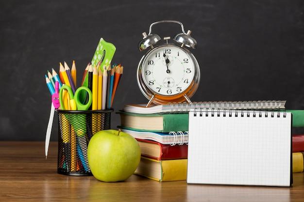 Widok z przodu na układ dnia edukacji na stole z notatnikiem