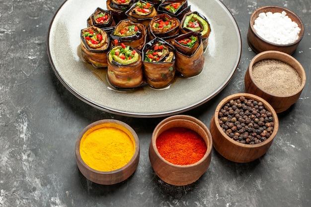 Widok z przodu nadziewane bułeczki z bakłażana na białym owalnym talerzu sól pieprz czerwony pieprz kurkuma na szarym tle